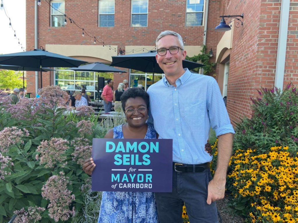 """Photo of Jillian Johnson and Damon Seils standing together outside Craftboro Brewing Depot and holding a sign that says """"Damon Seils for Mayor of Carrboro."""""""