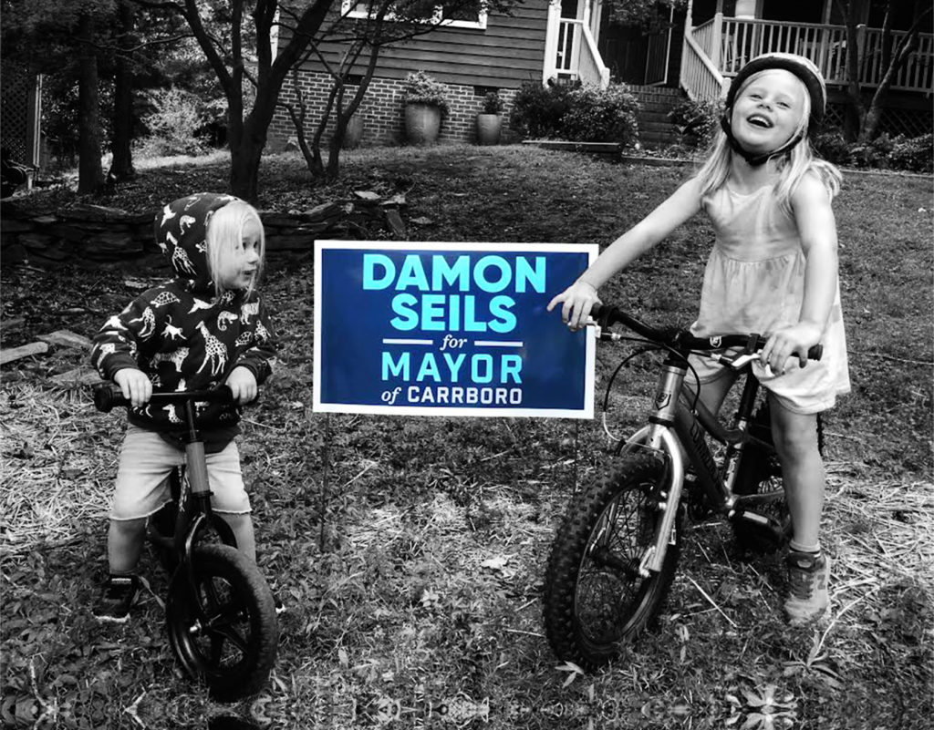 Photo of two children on bicycles standing next to a Damon Seils for Mayor of Carrboro yard sign.